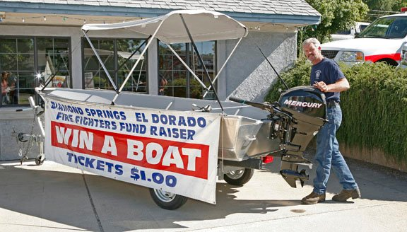 VOLUNTEER FIREFIGHTER Tom Anderson, 54, of Diamond Springs, stands by the fishing boat that will be won by a lucky ticket holder during the Diamond Springs/El Dorado Firefighters' Association Annual Labor Day Bazaar on Monday, Sept. 5. A 50 inch television is also one of the prizes. Democrat photo by Shelly Thorene