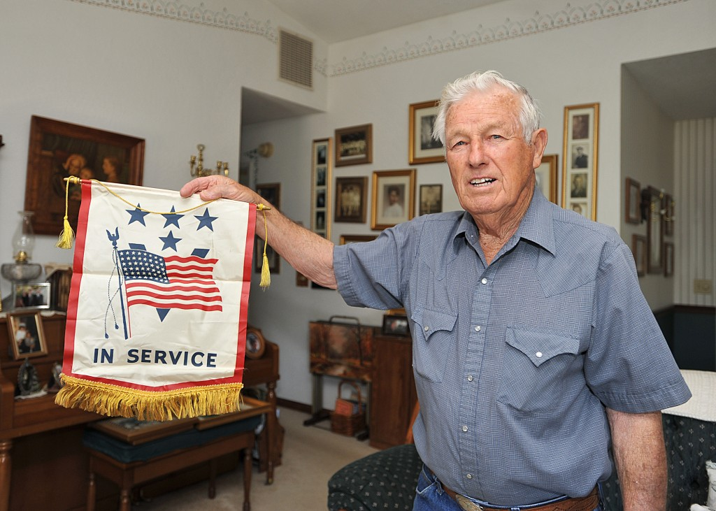 WORLD WAR II veteran, Daniel Hartman, 85 holds a banner, commonly used by families during World War II, indicating how many family members were serving during in the armed forces. Democrat photo by Shelly Thorene