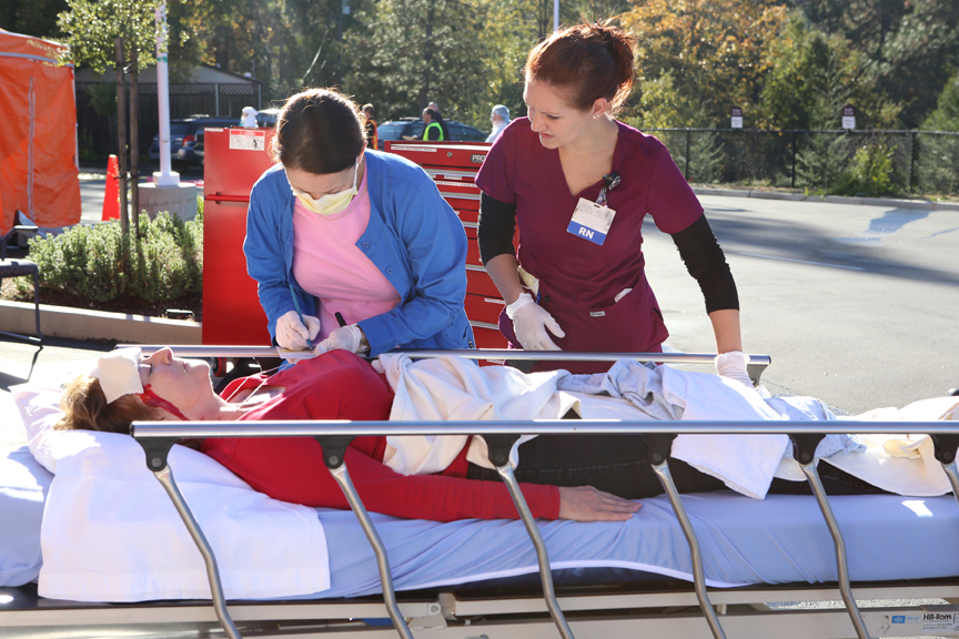 RNs Katrina Lemons, left, and Tana Richards assess the injuries of patient volunteer Diana Caudle during the mass-casualty incident drill held at Marshall Medical Center Thursday morning.