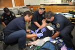EMERGENCY PERSONNEL simulate life-saving techniques on a volunteer cardiac patient at Station 49 in Diamond Springs during a training exercise. Left to right are engineer and  paramedic Spencer Morgan, Capt. Sean Wilson, firefighter and paramedic Karen Wollesen, and firefighter and paramedic Travis Parsons. Playing the role of the cardiac patient is Station 49 volunteer Steve Nichols. Democrat photo by Pat Dollins